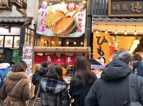 徳造丸 熱海駅前店。名物熱海みやげ販売と行列の即食屋台。食べ歩きやお土産の熱海グルメあわび串など。